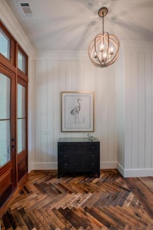 House foyer with herringbone pattern wood flooring