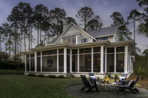 Gray house with screened back porch and fire pit area