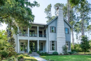 Two-story gray house with tabby stucco chimney