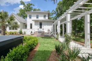 Two-story white house with trellis walkway